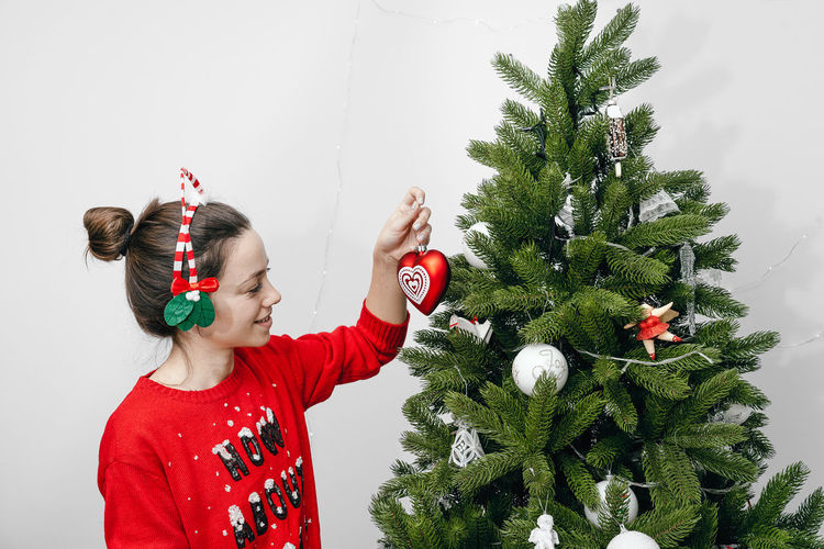 Red Decoration Ornament Smiling Smile One Person One Woman Only Women Young Women Indoors  Interior Tree Warm Clothing Christmas Decoration Christmas Winter Happiness Fun Christmas Ornament christmas tree Decorating The Christmas Tree Christmas Bauble Holiday Moments