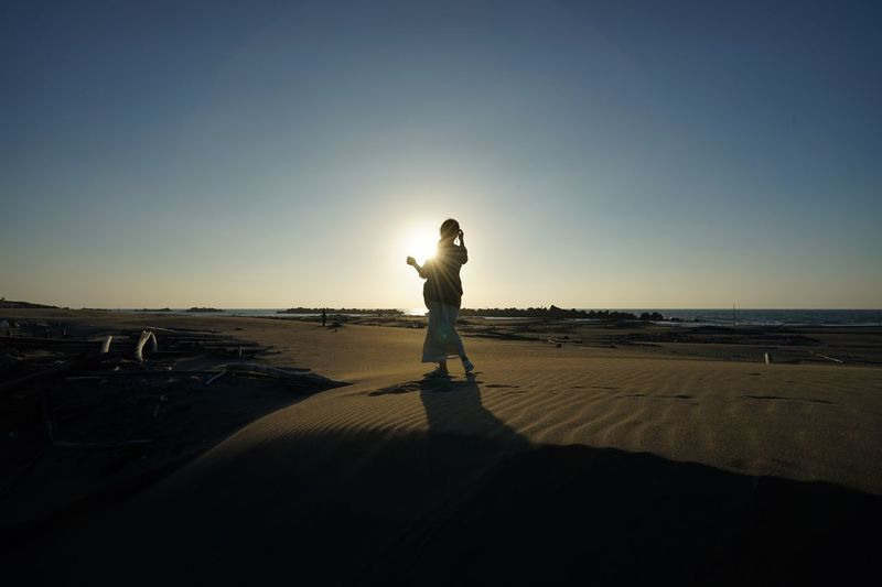 Silhouette woman standing at beach against clear blue sky