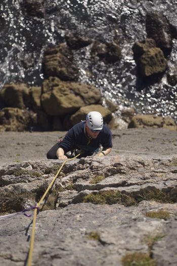 Man climbing rock on rocks