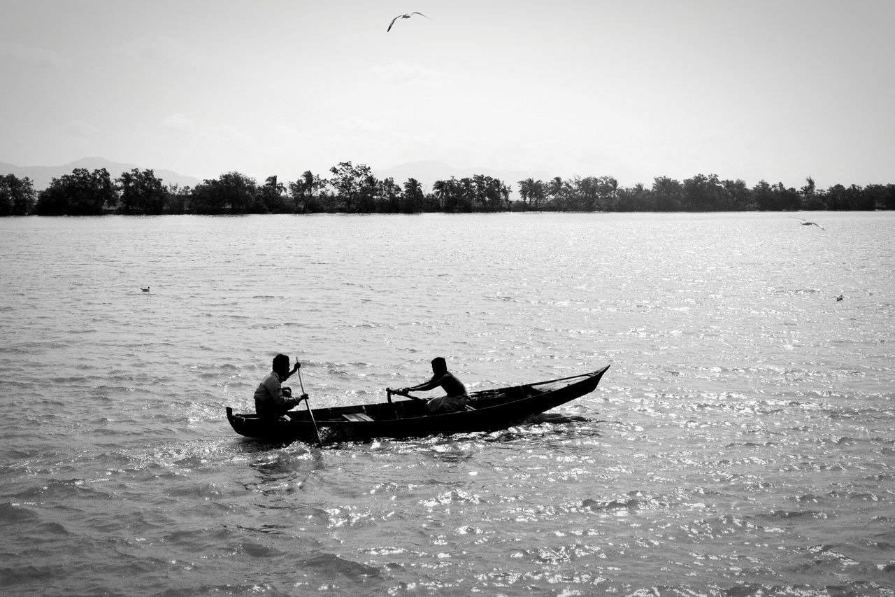 water, waterfront, real people, two people, men, transportation, nature, leisure activity, nautical vessel, adventure, day, silhouette, outdoors, rowing, togetherness, beauty in nature, sky, oar, people