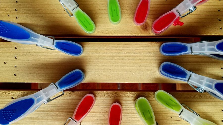 High angle view of colorful clothespins on wooden table