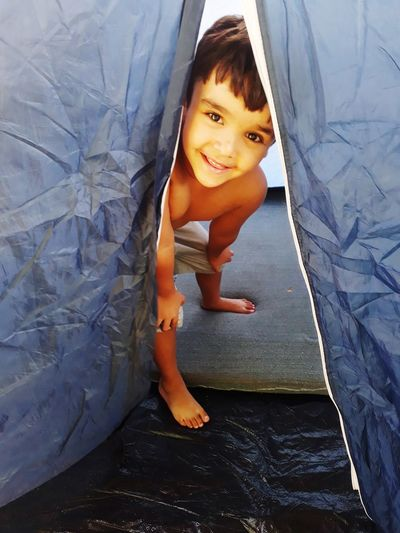 Portrait of cute boy smiling while inside tent