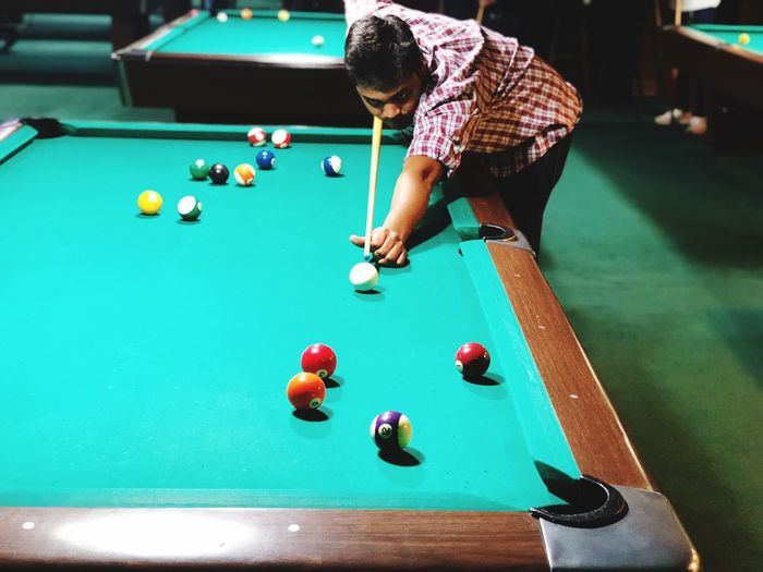 High angle view of young man playing pool ball