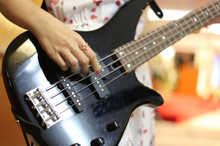 Midsection of woman playing electric guitar