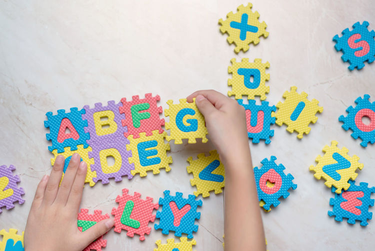 Cropped Hand Of Child Playing With Alphabets On Puzzles At Floor