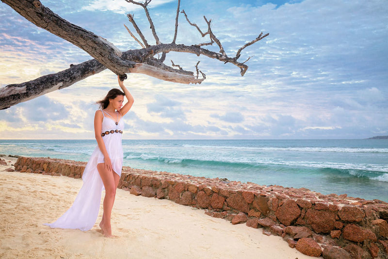 Full Length Of Woman Wearing White Dress Standing At Beach Against Sky