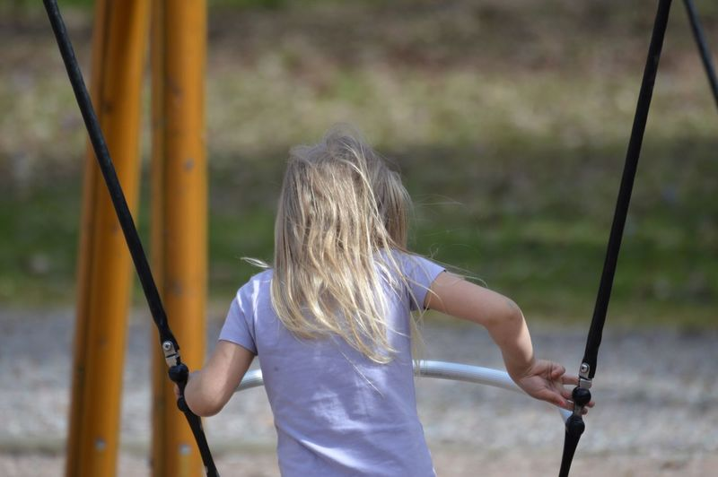 Rear view of girl playing at playground