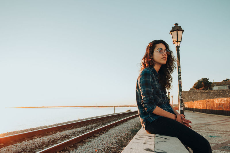 Woman sitting at railroad track against clear sky