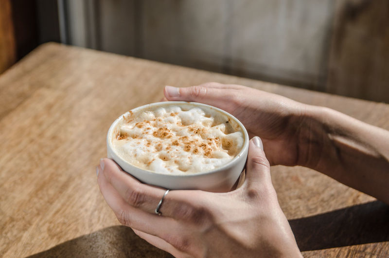 Cropped image of hands holding latte macchiato on table