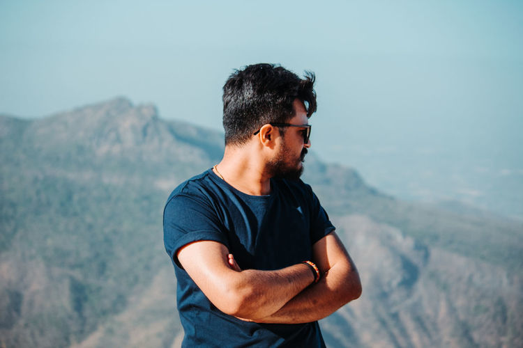 Young man wearing sunglasses standing against mountain