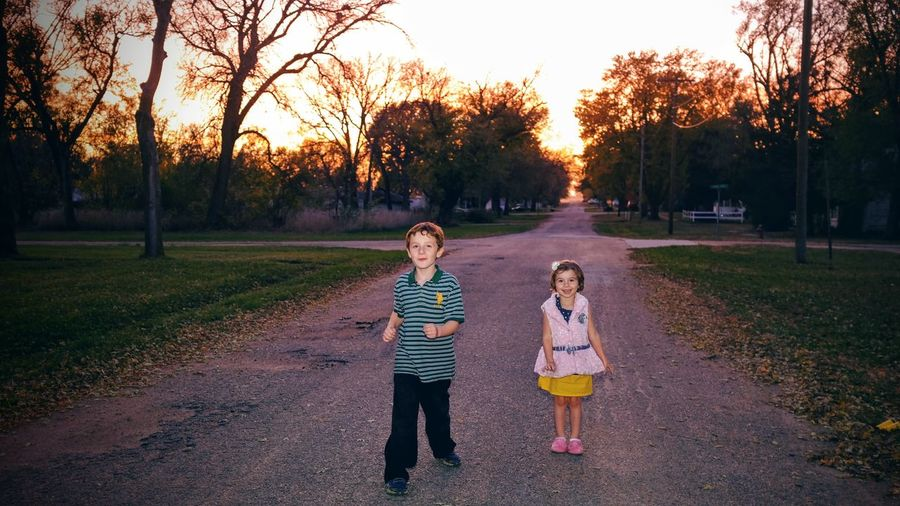 Full length portrait of boy and girl standing on road