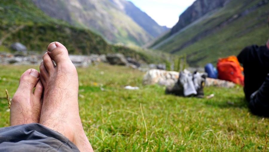Midsection of person relaxing on field