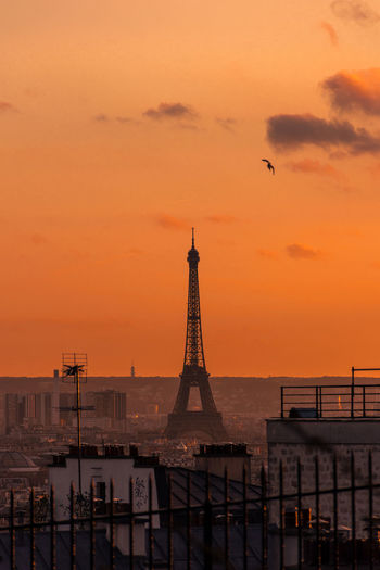 Aerial view of eiffel tower against sky in city during sunset