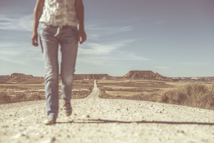 Low section of woman walking on dirt road at desert against blue sky