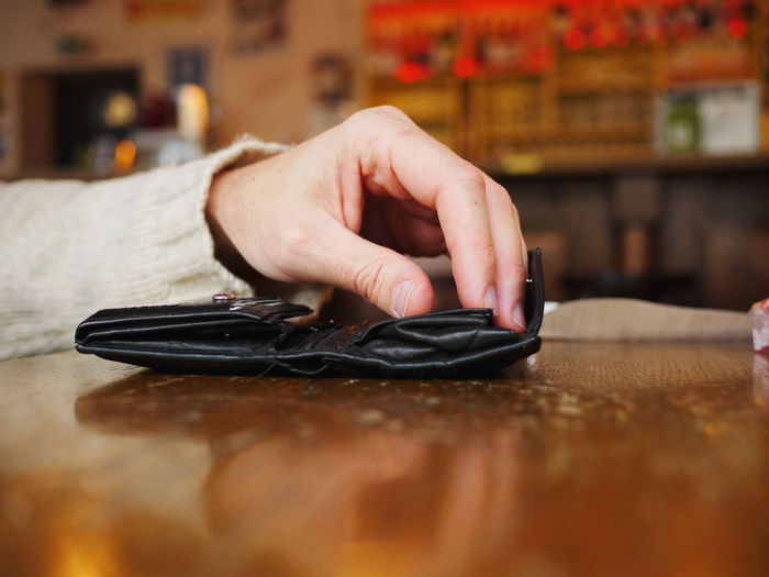 Close-up of hands with wallet at table