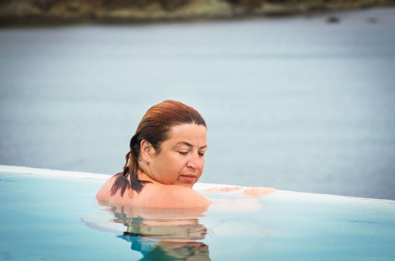 Woman swimming in infinity pool by sea
