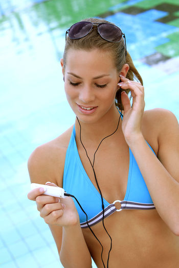 Young Woman Listening To Music At Poolside