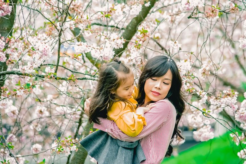 Beautiful Young Woman Carrying Daughter By Cherry Tree