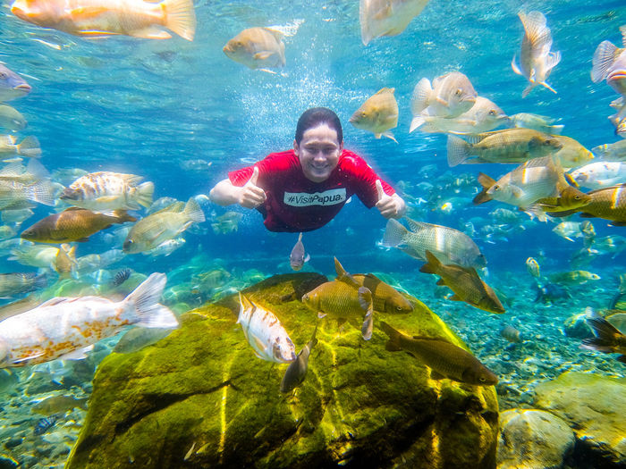 Full length of happy boy swimming underwater