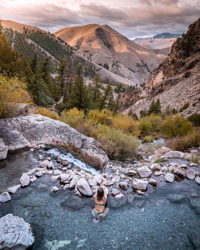 Woman in hot spring pools in mountains with a view