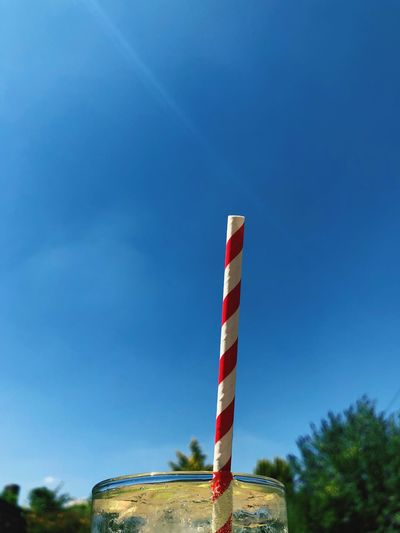 Paper straw and a pint glass on a hot summer day Lime And Soda Drink Paper Straws Straw Paper Straw Sky Blue No People Day Nature Plant Striped Outdoors Clear Sky Pole Tall - High Copy Space Flag Built Structure Tree Low Angle View Architecture Communication