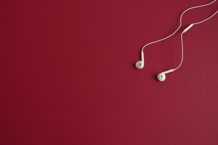Copy Space Red Indoors  Colored Background Studio Shot No People Single Object Close-up Still Life Headphones Music Listening Red Background Cable Simplicity Directly Above Connection High Angle View Earphones Technology White Playing Music
