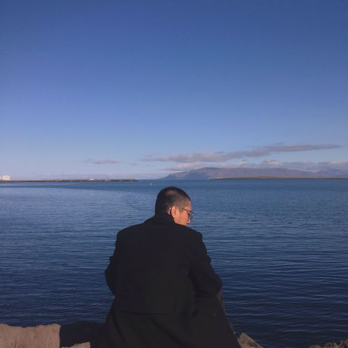 Rear view of man sitting on shore against sky