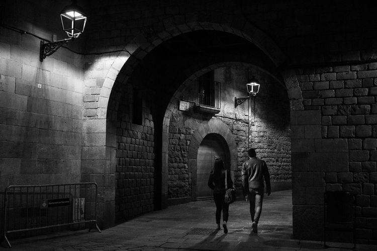Couple walking, old town Barcelona Brick Wall Arch Architecture Real People Walking Couple Old Town Old Streets Barcelona Catalunya Blackandwhite Obscure History Sant Felip Neri Alone Dark City Young Adult Wall Architecture Path