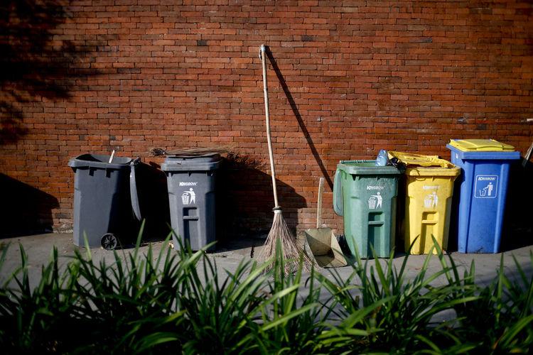 Garbage bin against brick wall