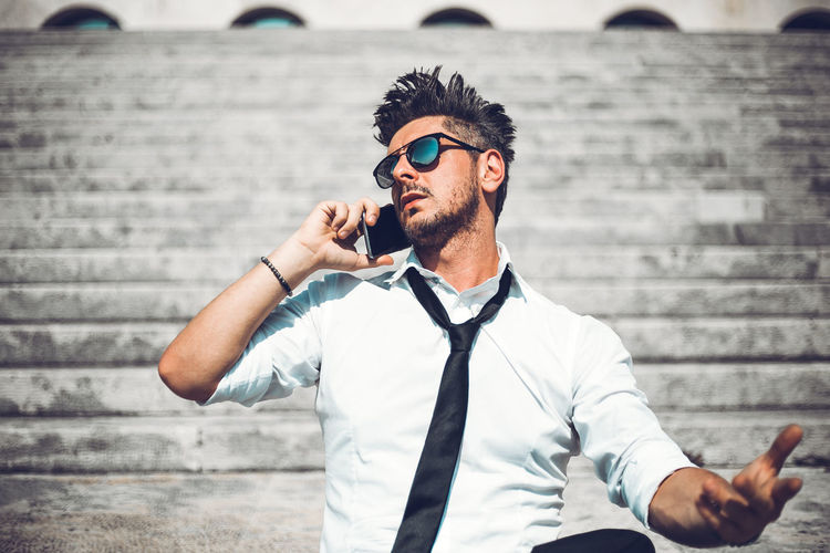 Low angle view of man talking on phone while sitting on steps