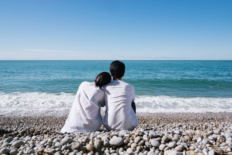 Rear View Of Couple Sitting At Beach Against Sky
