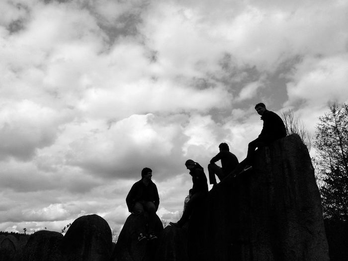Silhouette of people sitting on rocks / Silhouette von Personen, die auf Felsen sitzen Himmel Schwarzweiß Anonymous Anonym Menschen Gruppe Schatten Black And White Shadow Cloud - Sky Sky Nature Human Representation Low Angle View Sculpture Statue People Group Of People Silhouette Outdoors