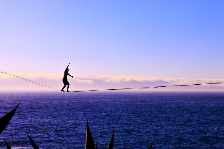 The Adventures Of Full Length Silhouette Sunset Outdoors Adventure Lifestyles Sea Men Nature Sport Slackline Slacklife Beauty In Nature Water Day Blue Horizon Over Water Sky Landscape Clouds Walking The Line Breathing Space