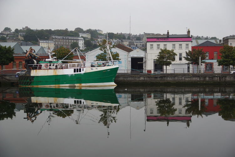 Boats moored in lake against buildings