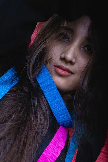 Portrait of young woman paper decoration against black background