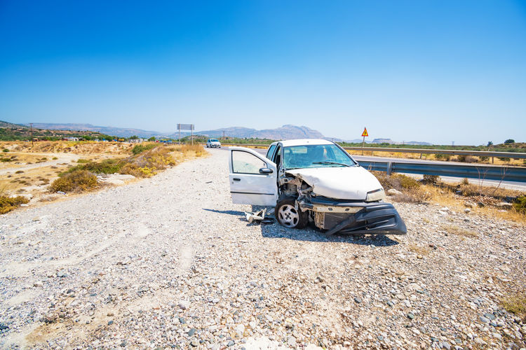 Abandoned car on road against clear blue sky