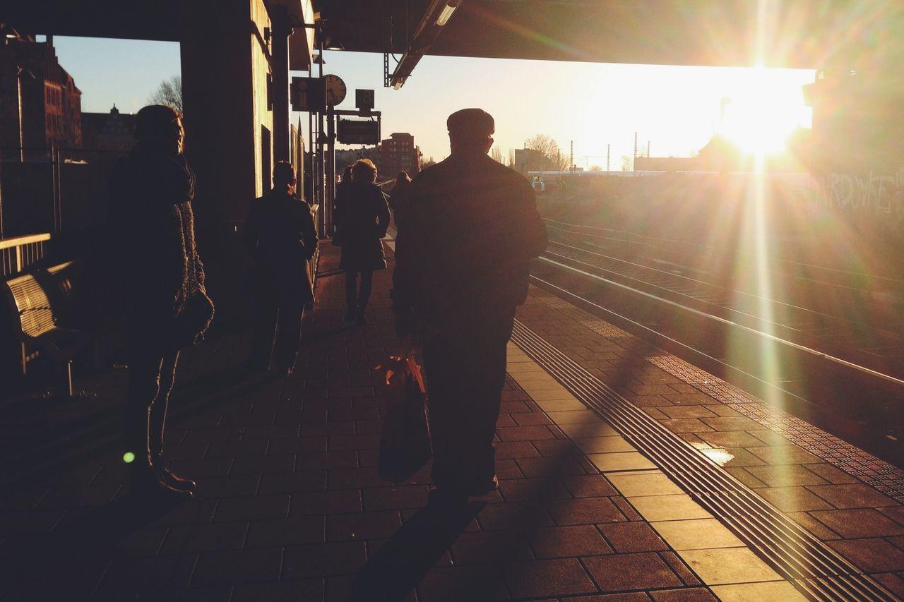 Silhouette people waiting on railway station platform