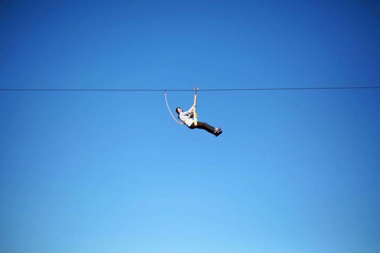 Low angle view of woman performing stunt on rope against clear blue sky