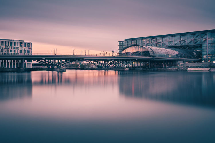 Railway bridge over river by berlin hauptbahnhof during sunset