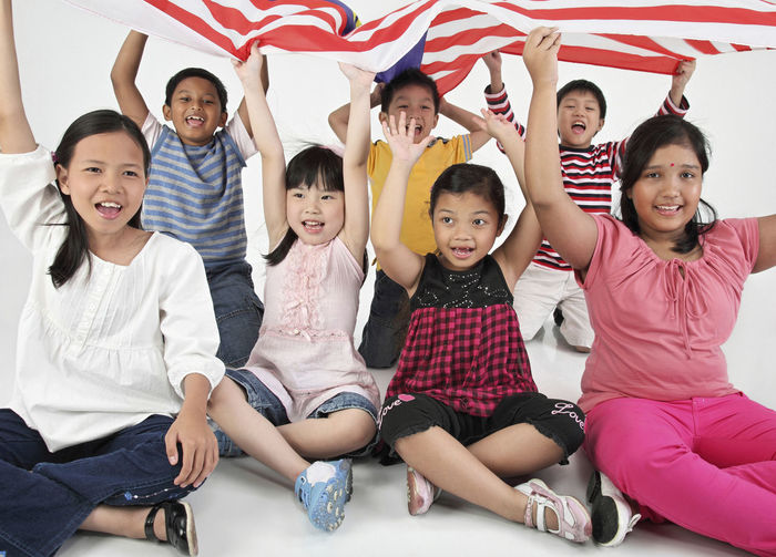 Portrait of cute friends holding malaysia flag against white background