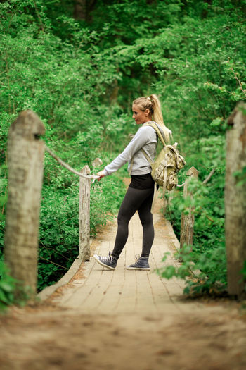 Side View Of Young Woman With Backpack Standing On Boardwalk In Forest