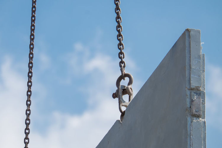 Low angle view of chain swing against sky