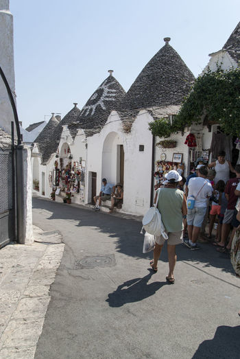 The magic of Alberobello's Trulli travel location - It was really amazing to know this particulars constructions full of charming and to ear the history about the Alberobello's Trulli in the Italy Apulia region (Puglia). The history said that the Alberobello's origins date back to the Middle Age. The settlers built the houses with stone and without cement and with the easiest way to demolish them in the case of an inspection by the Kingdom of Naples, thus avoiding paying taxes. Another interesting thing is the decorative pinnacles and symbols painted on many roofs of the trulli that were often used to identify the different religions of their inhabitants. Albelobelo Italia Viajes  2019 EyeEm Awards The Traveler - 2019 EyeEm Awards The Architect - 2019 EyeEm Awards The Photojournalist - 2019 EyeEm Awards The Street Photographer - 2019 EyeEm Awards Italy EyeEm Gallery EyeEm Best Shots Eyeem4photography Architecture Built Structure Building Exterior Real People Building Men City Sunlight People Full Length Street Nature Lifestyles Day Walking Adult Group Of People Incidental People Sky Women