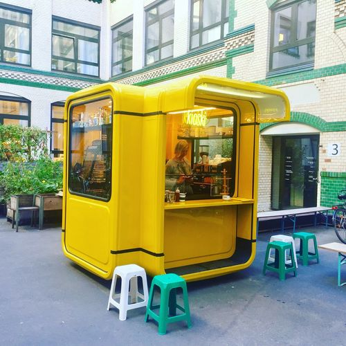 Yellow bus on street against buildings in city