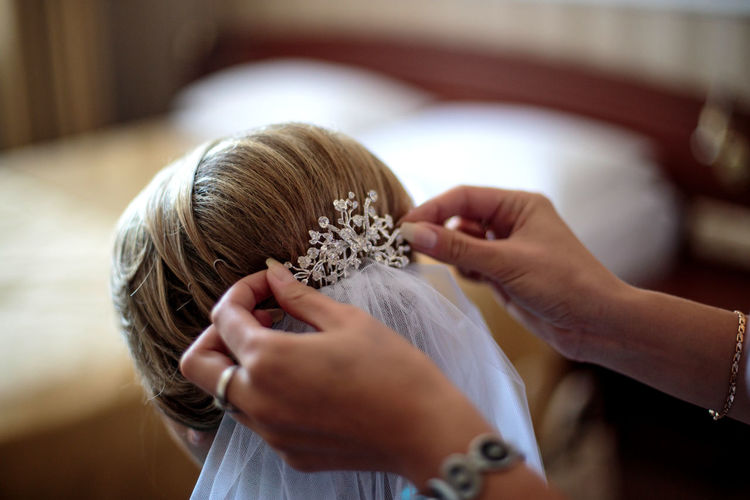 Cropped Hands Of Beautician Dressing Bride At Home