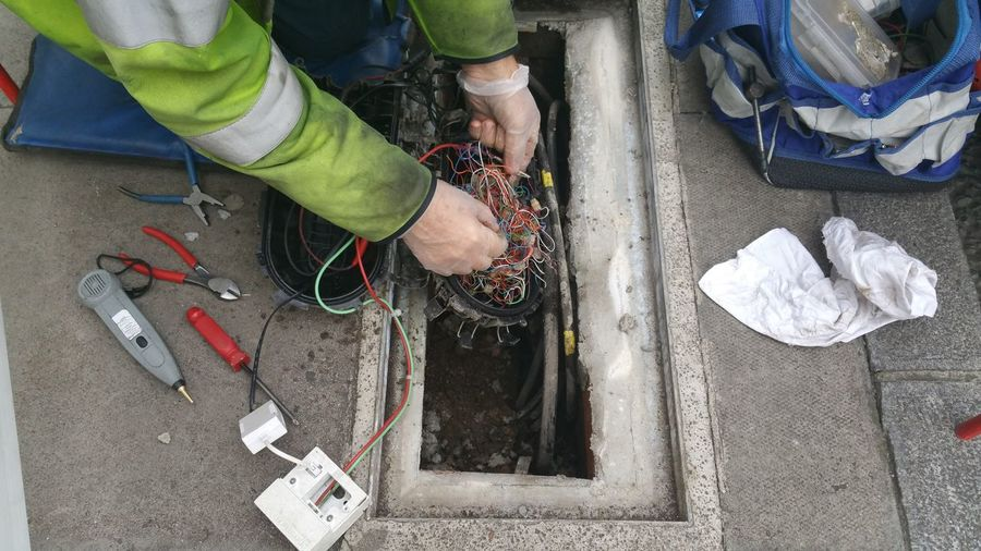Telecom engineer working on street Communication Telecommunication Engineer British Telecom Wires Cables And Wires Street Workers At Work Messy Repairing Maintainance Error Construction Fixing Tools Business Finance And Industry