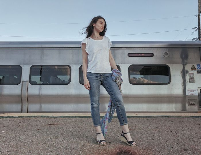 Full length of young woman looking away while standing on platform against train