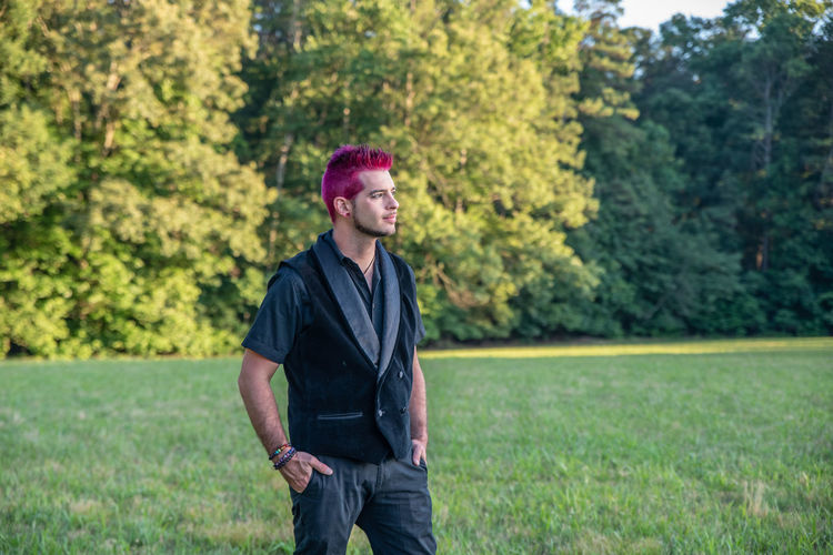 Man with pink hair standing outdoors