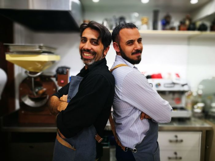 Portrait of smiling owners standing back to back in commercial kitchen