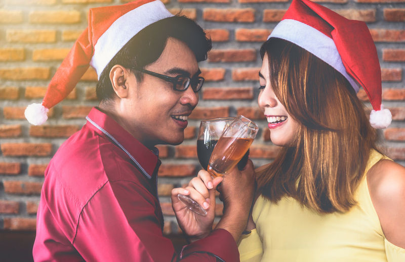Young Friends In Santa Hat Enjoying Drinks Against Brick Wall At Restaurant